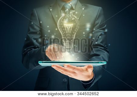Creative company give you their creativity and ideas. Hands with digital tablet and graphics light bulb - symbols of idea, creative thinking, innovations and intelligence. stock photo
