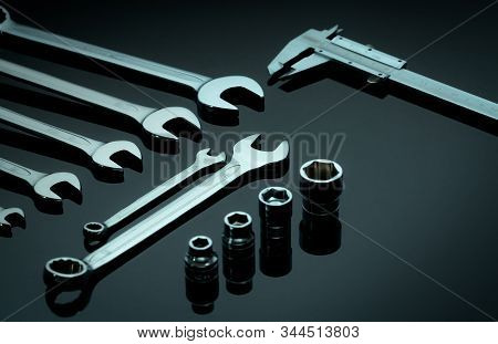 Set of chrome wrenches or spanners, hexagon socket, and vernier caliper on dark table in workshop. Chrome vanadium spanner wrench. Silver wrenches. Mechanic tools. Hardware for service technician. stock photo