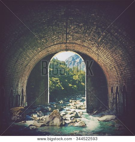 Digital photo manipulation of an alpine mountain stream running through an old arched brick tunnel. Nature and wilderness meet vintage architecture. Portal into another world concept. stock photo