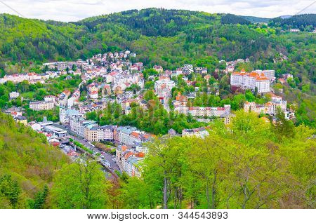 Top aerial panoramic view of Karlovy Vary (Carlsbad) spa town with colorful beautiful buildings, Tepla river and hills of Slavkov Forest with green trees, West Bohemia, Czech Republic stock photo