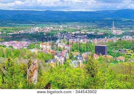 Top aerial panoramic view of Karlovy Vary (Carlsbad) spa town with colorful beautiful buildings, Slavkov Forest with green trees and Ore Mountain range background, West Bohemia, Czech Republic stock photo