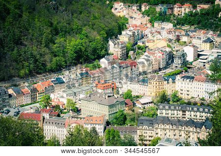 Karlovy Vary (Carlsbad) historical city centre top aerial view with colorful beautiful buildings, Slavkov Forest hills with green trees on slope, close-up, West Bohemia, Czech Republic stock photo