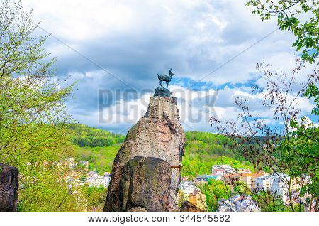 Chamois Statue Socha Kamzika at Deer Jump Jeleni Skok Lookout with Karlovy Vary (Carlsbad) colorful beautiful buildings and Slavkov Forest hills background, West Bohemia, Czech Republic stock photo