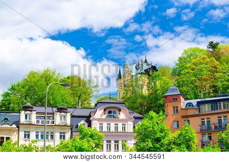 Colorful beautiful traditional buildings in Karlovy Vary (Carlsbad) historical city centre , blue sky white clouds background, West Bohemia, Czech Republic stock photo