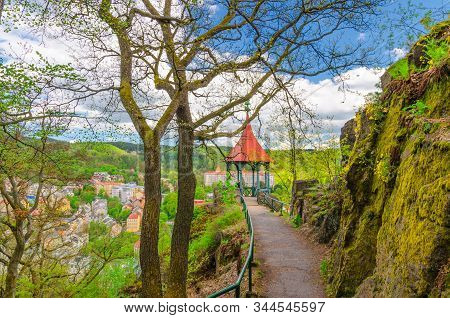 Mayer Gloriette wooden gazebo at Deer Jump Jeleni Skok Lookout with top aerial view of Karlovy Vary (Carlsbad) historical city centre, path with trees, big stone rock, West Bohemia, Czech Republic stock photo