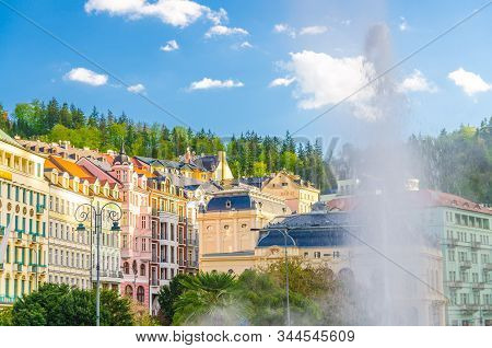 Hot spring geyser Vridlo at Karlovy Vary Carlsbad historical city centre, colorful beautiful buildings, blue sky white clouds, forest with green trees background, West Bohemia, Czech Republic stock photo