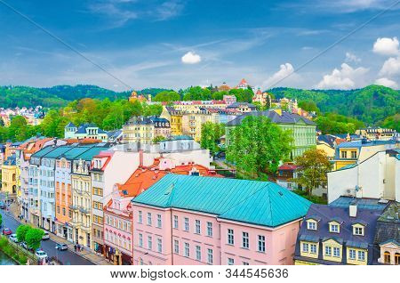 Karlovy Vary (Carlsbad) historical city centre aerial view with Tepla river embankment, colorful beautiful buildings, skyline with forest hills green trees background, West Bohemia, Czech Republic stock photo