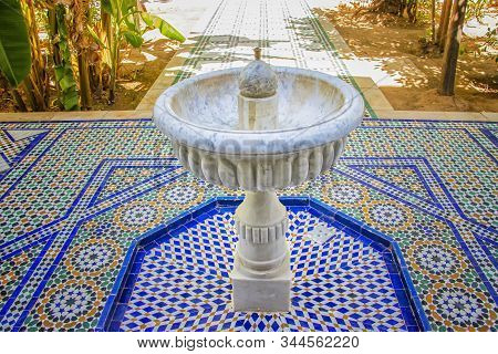 White stone fountain in the middle of green garden of Islamic palace. Its in Morocco. The fountain stands on blue-white tiles with typical Arab and Berber ornaments stock photo