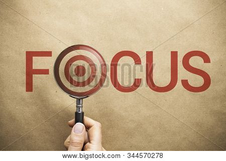 Woman hand holding magnifying glass over the word focus written on paper background. Target symbol in the middle of magnifier. Correct focus leads to targeted success. stock photo