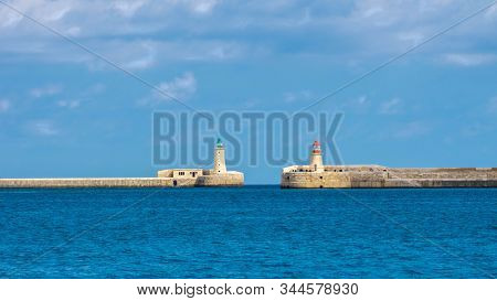 Seascape with Grand Harbour gate to Mediterranean sea with two lighthouses in Valletta, Malta stock photo