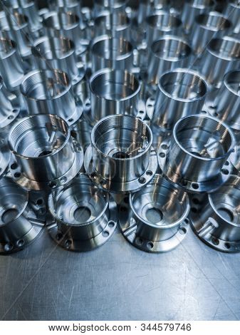 a large batch of shiny metal cnc aerospace parts - close-up with selective focus for industrial manufacturing background stock photo