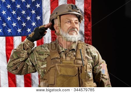 Front view of old military officer saluting and looking away. Portrait of bearded american veteran in uniform and helmet posing on black background with flag. Concept of military, army. stock photo