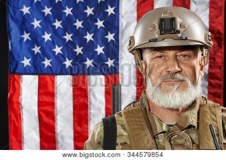 Front view of old military officer with gun on shoulder looking at camera. Portrait of bearded american veteran in uniform and helmet posing on black background with flag. Concept of military, army. stock photo