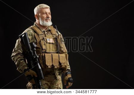 Front view of old military officer holding sniper rifle and looking away. Portrait of bearded american veteran in uniform posing with gun on black studio background. Concept of military, army. stock photo