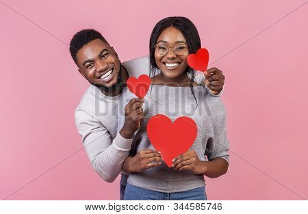 St. Valentines day concept. Cheerful afro couple in love holding red valentines cards and embracing, pink studio background stock photo