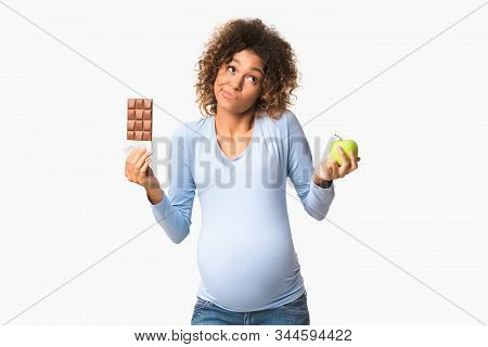 Puzzled expecting woman choosing between sweets and fruits, holding apple and chocolate, white background stock photo