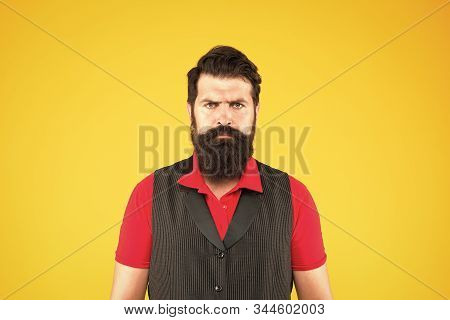 Hospitality staff. Restaurant cafe staff wanted. Man bearded hipster with mustache wear vest and shirt uniform yellow background. Shop staff concept. Salesman cashier career. Hiring shop store worker. stock photo