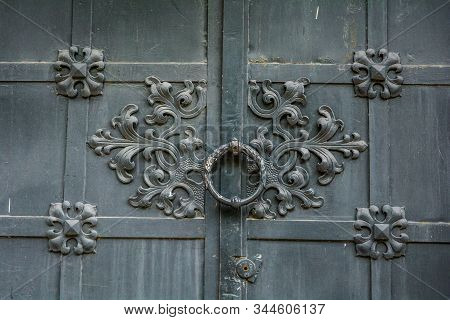 Close-up of detail of ancient vintage metal door with cast iron floral deorative ornament stock photo
