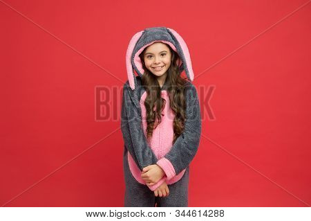 Happy girl in bunny pajamas. Lifestyle concept. Rest and relax. Cute bunny kid on red background. Baby animal character role. Adorable bunny. Gorgeous girl in bunny costume. Child in rabbit kigurumi. stock photo