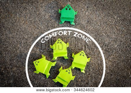Exit from the comfort zone concept. Dark green frog jump out of the comfort zone while other light green frogs are still inside the circle of comfort zone. stock photo