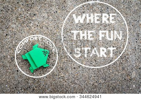 Exit from the comfort zone concept. Dark green frog jump out of the circle of comfort zone stock photo
