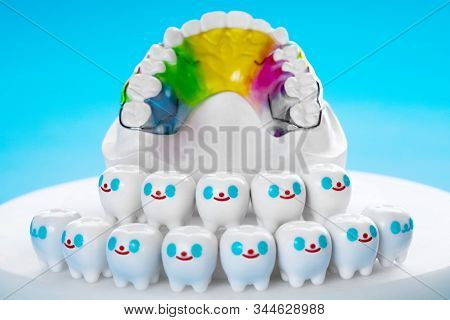 Dental retainer orthodontic appliance and dental tools on the blue background. stock photo