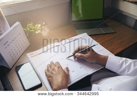 Calendar reminder event concept.Man hand planner or organizer writing on diary book and 2020 Calendar page.Student planning appointment,noted and count Down schedule day on Calender stock photo
