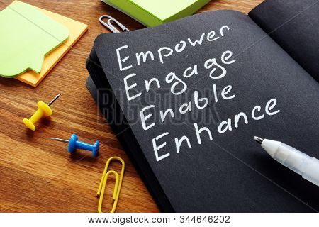 Empower engage enable enhance words written in the notepad. stock photo