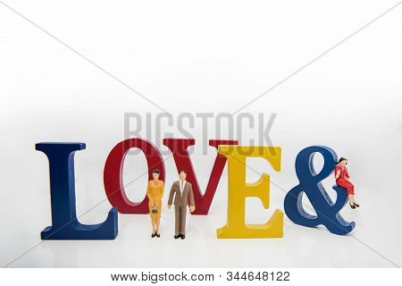 Love triangle. Abstract photo of love and lovers. Big wooden letters with small plastic people figures. stock photo