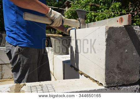 Bricklayer builder laying autoclaved aerated concrete blocks, aac for new house wall.  Autoclaved aerated concrete blocks walling installation stock photo