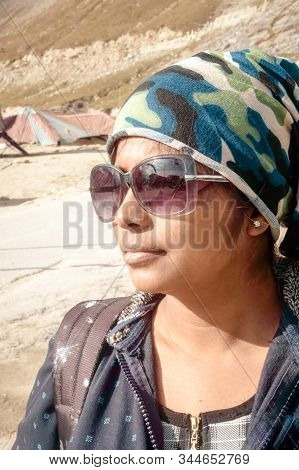 Front Side portrait of young adult beautiful woman (asian and indian ethnicities) with smart casual look headscarf and sunglasses looking away isolated from nature background. Headshot Close up. stock photo