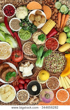 Healthy vegan super food collection with fruit, vegetables, nuts, spice, dips, grains, tofu, falafel & tofu burgers  High in vitamins, minerals, antioxidants, dietary fibre & smart carbs. Flat lay. stock photo