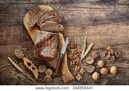 High fibre fig and walnut rye bread. High in vitamins, antioxidants & omega 3 with low gi. Health food to reduce high blood pressure, cholesterol & optimise a healthy heart on rustic wood. Flat lay. stock photo