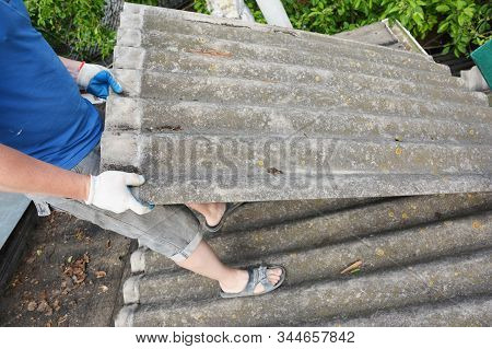 Asbestos removal roofer roof works. House with old, danger asbestos roof tiles repair and renovation.  Risks of Asbestos Roofs, Asbestos Roof Removal. stock photo
