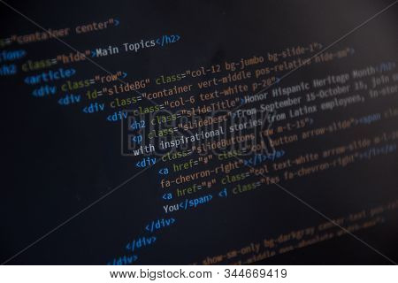 Source code or HTML code on screen of computer, Close up css code on monitor screen with black background, binary code on dark background stock photo