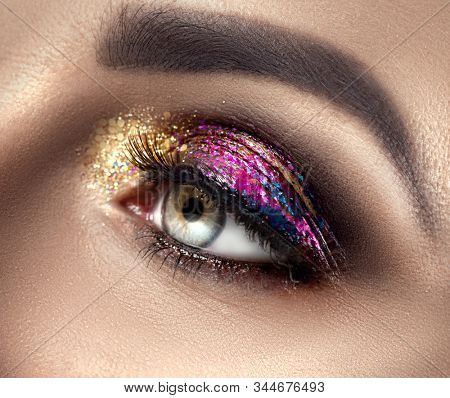 Beautiful Eye Make-up with colorful sparks. Beauty bright fashion holiday smoky eye makeup. Make up sample, close-up of model woman green color eye. Purple and golden glitter eyeshadows stock photo