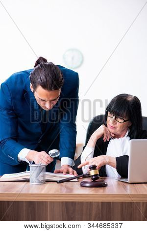 Young intern asking senior judge for advice stock photo