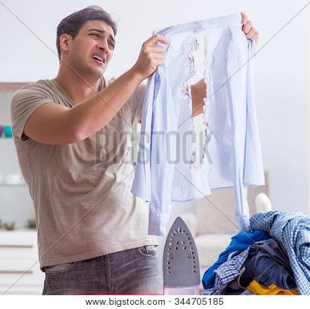 Inattentive husband burning clothing while ironing stock photo