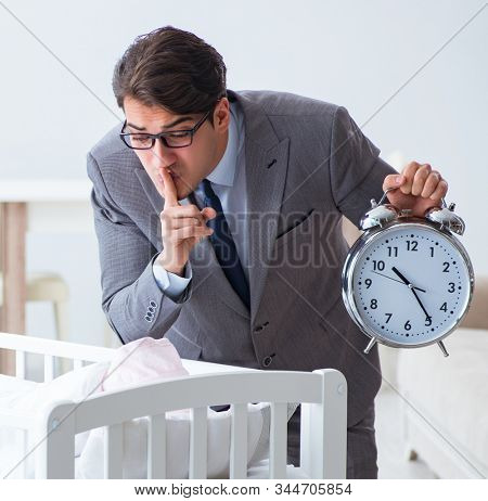 Young businessman trying to work from home caring after newborn stock photo