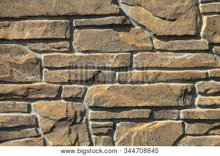 Beige-colored decorative stone wall, texture, background. Tan or light-brown stones of irregular shape in the wall construction. Decorative stone laying. The design of stylish exterior stock photo
