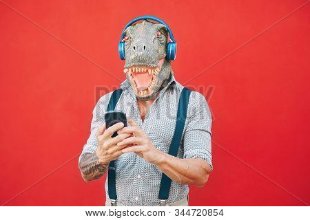 Senior fashion man wearing t-rex mask using mobile smartphone listening music with headphones - Crazy bizarre hipster guy having fun with new technology - Funny and absurd surreal concepts stock photo