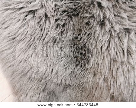 Fur rug, the surface of the sheepskin. Gray fur with a long NAP. A feeling of warmth and softness. stock photo