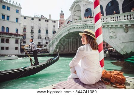 woman sitting near rialto bridge in venice italy looking at grand canal with gondolas stock photo
