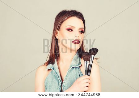 Emphasize femininity. Girl apply powder eye shadows. Looking good and feeling confident. Makeup dark lips. Attractive woman applying makeup brush. Professional makeup supplies. Makeup artist concept stock photo