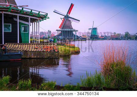 Wonderful traditional old dutch windmills in the popular Zaanse Schans touristic village and museum at misty morning, near Amsterdam, Zaandam, Netherlands, Europe stock photo