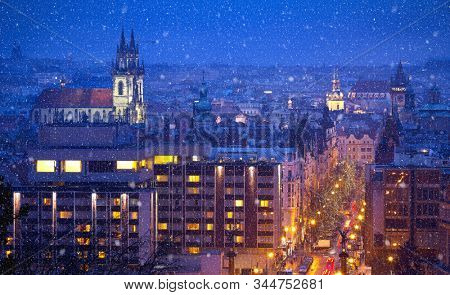 Prague Czech Republic. View at nighttime winter town with falling snow tower and broach cathedral. Illuminated with illumination street and Church of Our Lady Before Tyn aerial view. stock photo