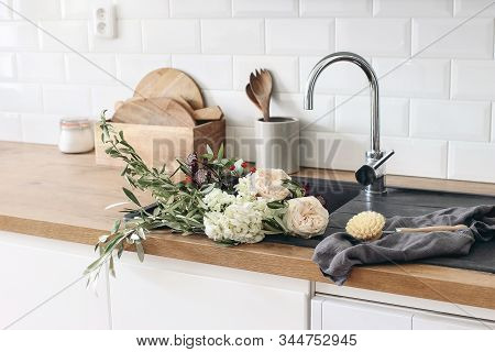 Closeup of kitchen interior. White brick wall, metro tiles, wooden countertops with kitchen utensils. Roses flowers in black sink. Modern scandinavian design. Home staging, cleaning concept. stock photo
