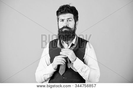 How to tie necktie. Start with your collar up and the tie around your neck. How to tie simple knot. Art of manliness. Man bearded hipster try to make knot. Different ways of tying necktie knots stock photo