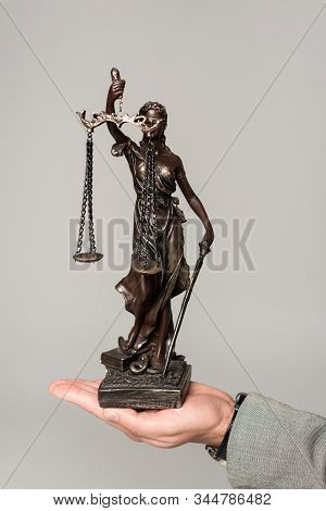 cropped view of lawyer holding themis statue isolated on grey stock photo