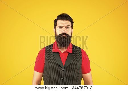 Shop staff concept. Salesman cashier career. Hiring shop store worker. Hospitality staff. Restaurant cafe staff wanted. Man bearded hipster with mustache wear vest and shirt uniform yellow background. stock photo